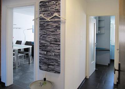 Diele mit Garderobe und geöffneten Türen zu Küche und Wohnzimmer
