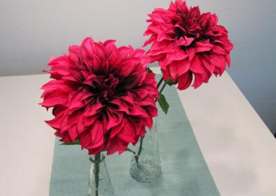 Zwei rote Blumen in Vasen auf einem Tisch
